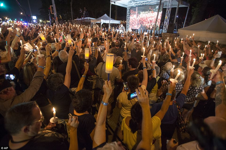 Celebration: Visitors hold aloft their candles in celebration as they watch themselves being projected onto a screen behind a stage at the Graceland vigil