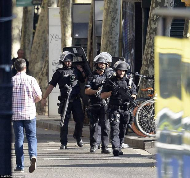 Pictured: Armed policemen arrive in a cordoned-off area after a van ploughed into a crowd in Barcelona