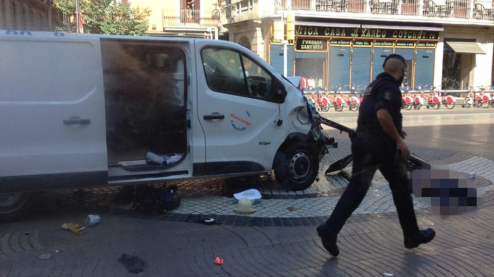 In Barcelona, a hired van (pictured), registered to rental company Telefurgo, rammed into scores of holidaymakers and their children. The crumpled van is pictured as a body lies on the ground