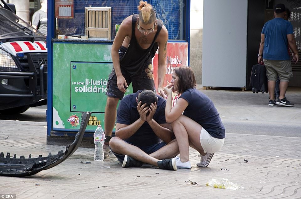 A man sits on the pavement with his head in his hands after the tragic attack, now being treated as a terrorist incident