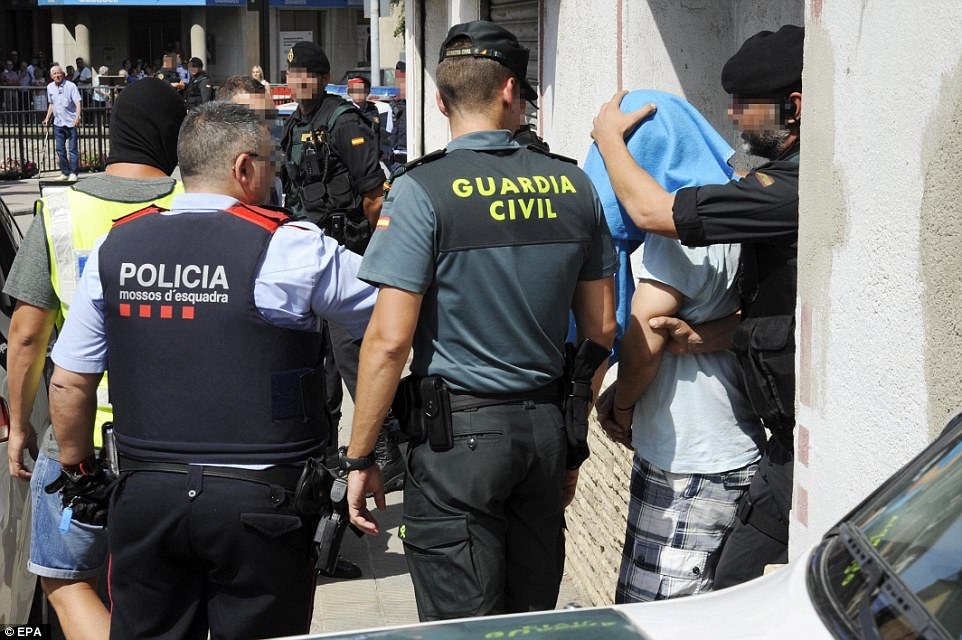 Spanish security forces escort a friend of two Moroccan-born brothers linked to the Barcelona plot after arresting him in the town of Ripoll, Catalonia