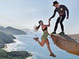 Tricksy: More than 350 metres above the Atlantic Ocean, student Marcelle Rangel da Cunha smiles as her fiancé Luiz Fernando Candeia helps her dangle over the rocky edge