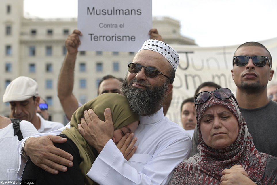 A man comforted a woman in the city during the protest which involved hundreds of people condemning the violence