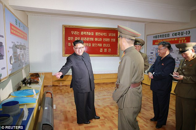 Kim Jong-un stands with his back to a new design of a missile which is displayed on a wall