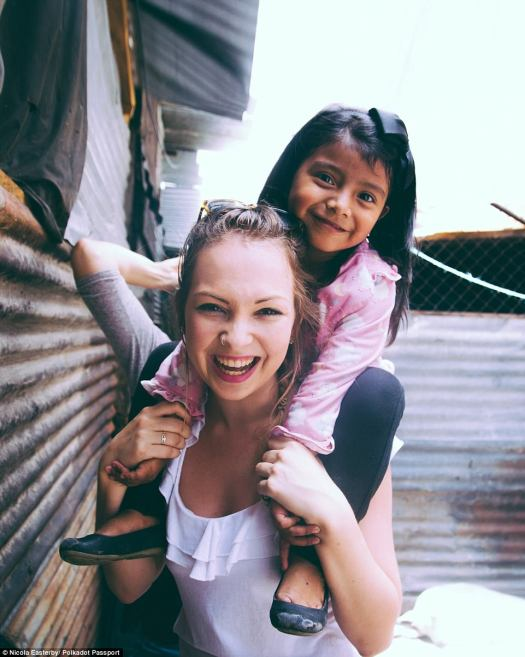 She has travelled to more than 46 countries - and still counting! (pictured with a little girl in Guatemala in Central America)