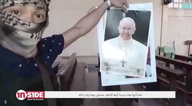Una imagen del Papa Francisco es sostenida por un jihad de habla inglesa en una iglesia de Marawi antes de que sea rasgada en medio & nbsp;
