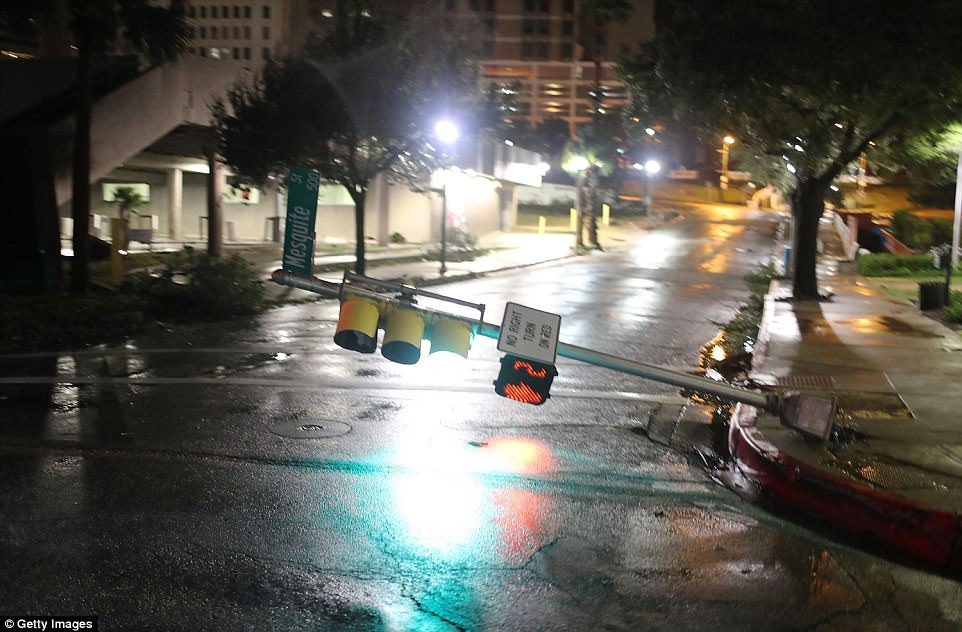 Texas residents woke up Saturday morning to the massive damage caused by Hurricane Harvey as it slammed into the Texas coast with winds of up 130mph (Pictured, a street light is knocked off its base by Harvey's winds in Corpus Christi)