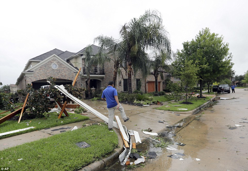 Texas has been left reeling by Harvey after the monstrous storm slammed into the state Friday evening as a Category Four hurricane. Pictured: A contractor walks over fallen debris from Hurricane Harvey on Saturday in Missouri City, Texas