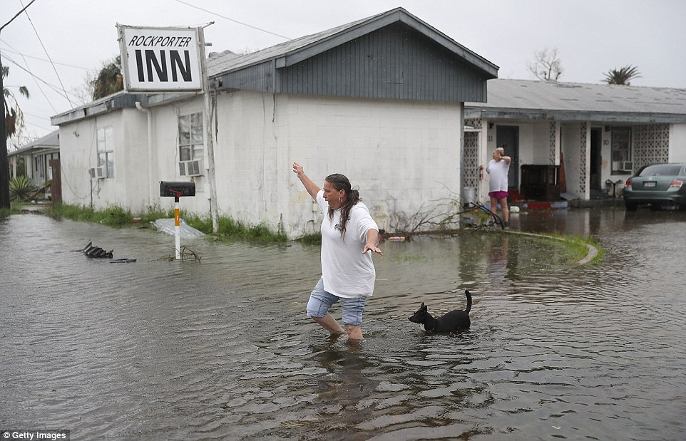 Valerie Brown and her dog walk through a flooded area after leaving the apartment that she rode out Hurricane Harvey in in Rockport