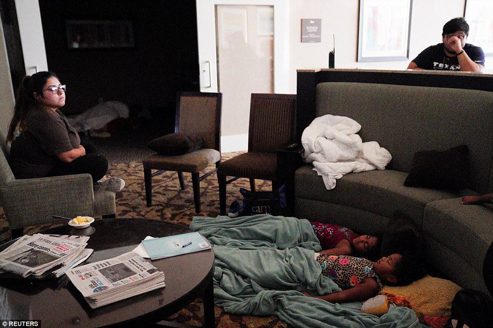 Children sleep in a hotel lobby waiting out Hurricane Harvey in Victoria, Texas, on Saturday