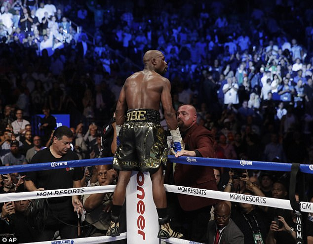 Mayweather jumps on the ropes to celebrate his victory after stopping McGregor in the 10th