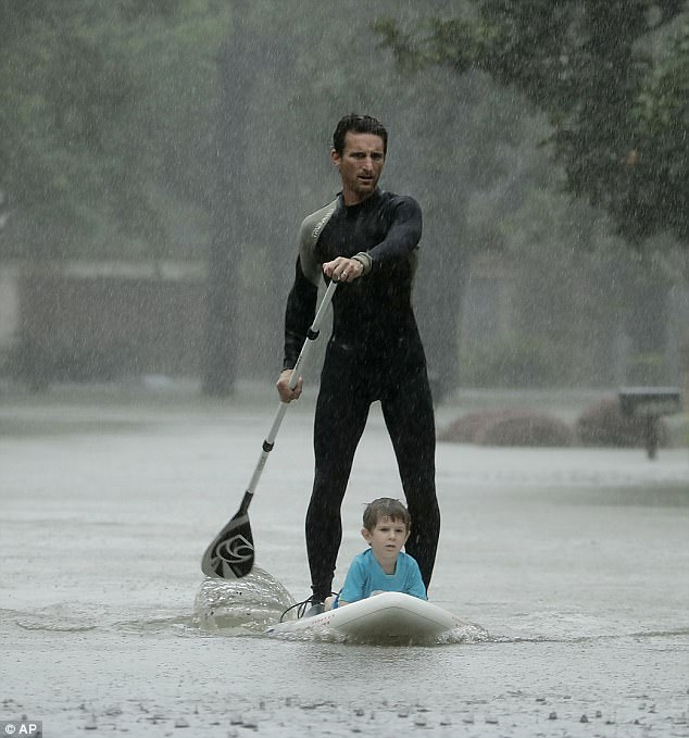 Alexandre Jorge was pictured paddle boarding four-year-old Ethan Colman to safety in a flooded neighborhood in Houston on Monday