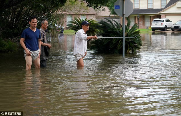 A man points with his walking stick in the Tropical Storm Harvey floodwaters in north western Houston on Wednesday
