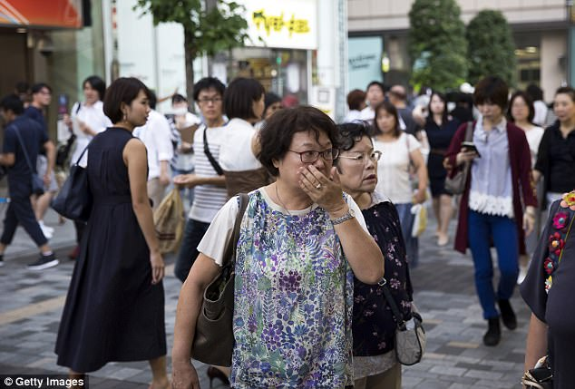 Meanwhile in Japan pedestrians were shocked as they walked past a monitor revealing news of the blast