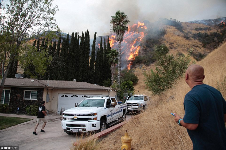 The blaze comes dangerously close to this hillside property where emergency responders have parked in the driveway