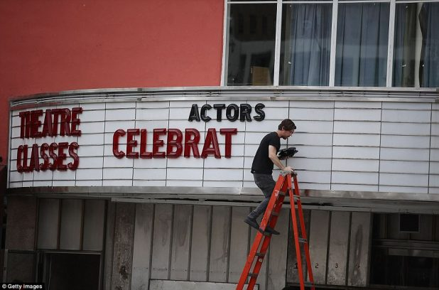 Matt Scally takes letters off the marquee at the Actor's Playhouse at the Miracle Theatre in Miami, Florida on Wednesday