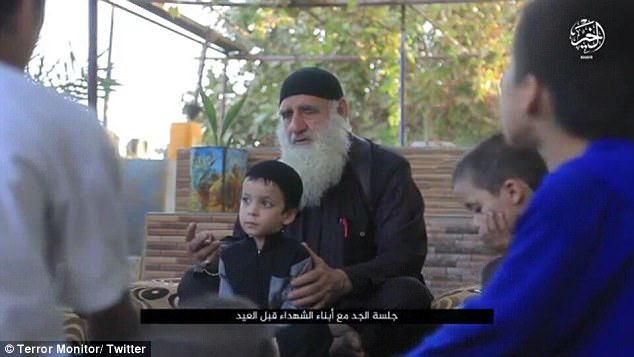 A boy, who only looks around three or four-years-old, sits in front of the elderly Islamic preacher