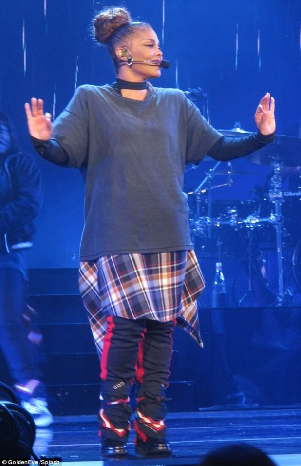 Keeping it casual: Later in the gig, Janet donned a navy sweatshirt over a grungy checked dress