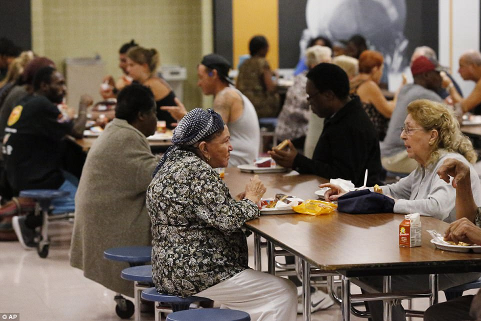 People at a Red Cross shelter set up at North Miami Beach Senior High School eat lunch on Friday