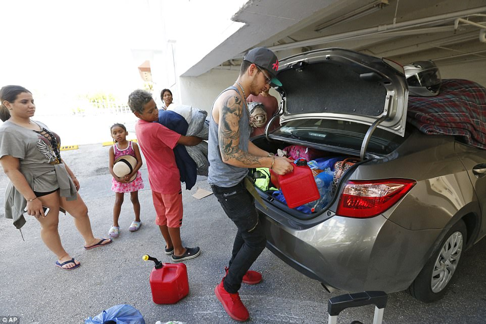 Luis Garcia, right, packs a car that he and five other members of his extended family will use to evacuate north from their home in Miami Beach, Fla, Friday, Sept. 8, 2017