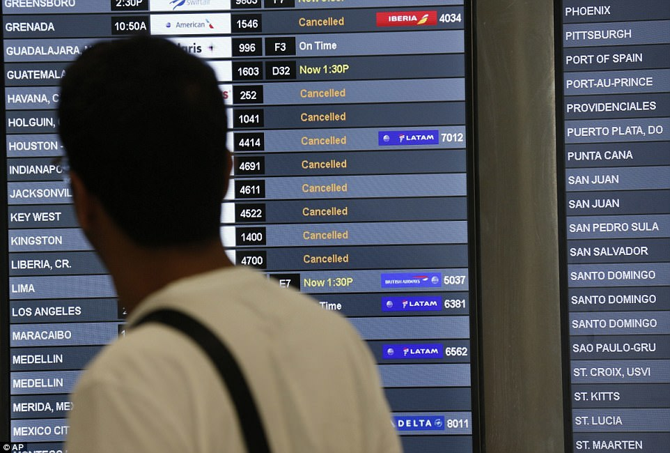A traveler looks at a monitor listing canceled flights at Miami International Airport on Friday