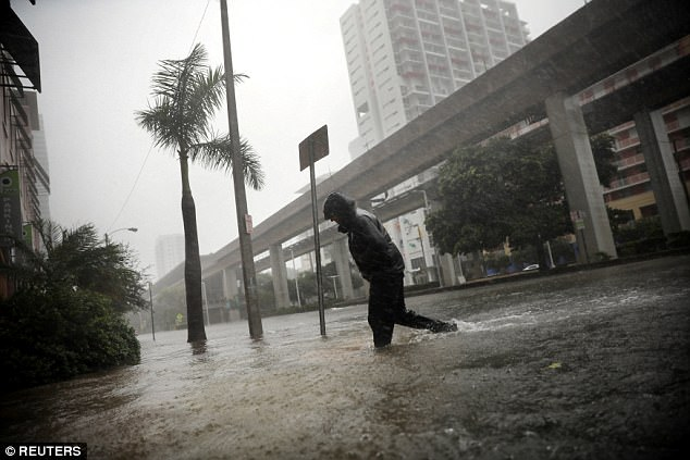 A local resident walks across a flooded street in downtown Miami on Sunday as Hurricane Irma arrived in full force