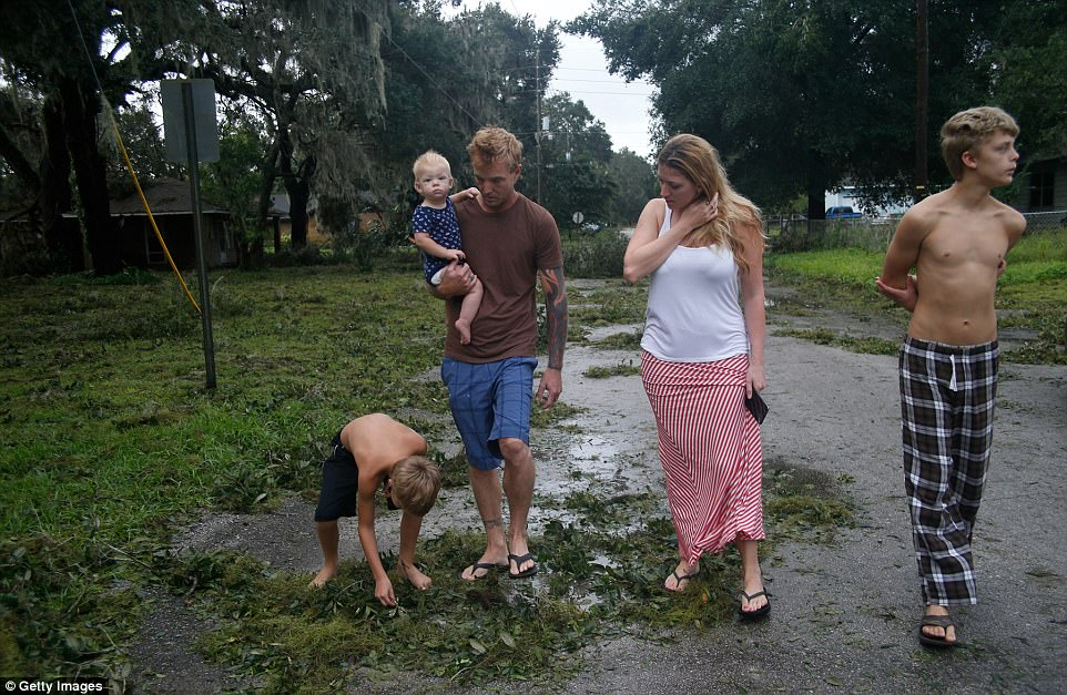 Zachary Harrison, his fiance Cheyanne O'Donnell and their three children, Jaiden, 14, Jackson, 9, and Ella, 10-months, get their first look at the damage to their neighborhood caused by Hurricane Irma on Monday in Fort Meade, Florida