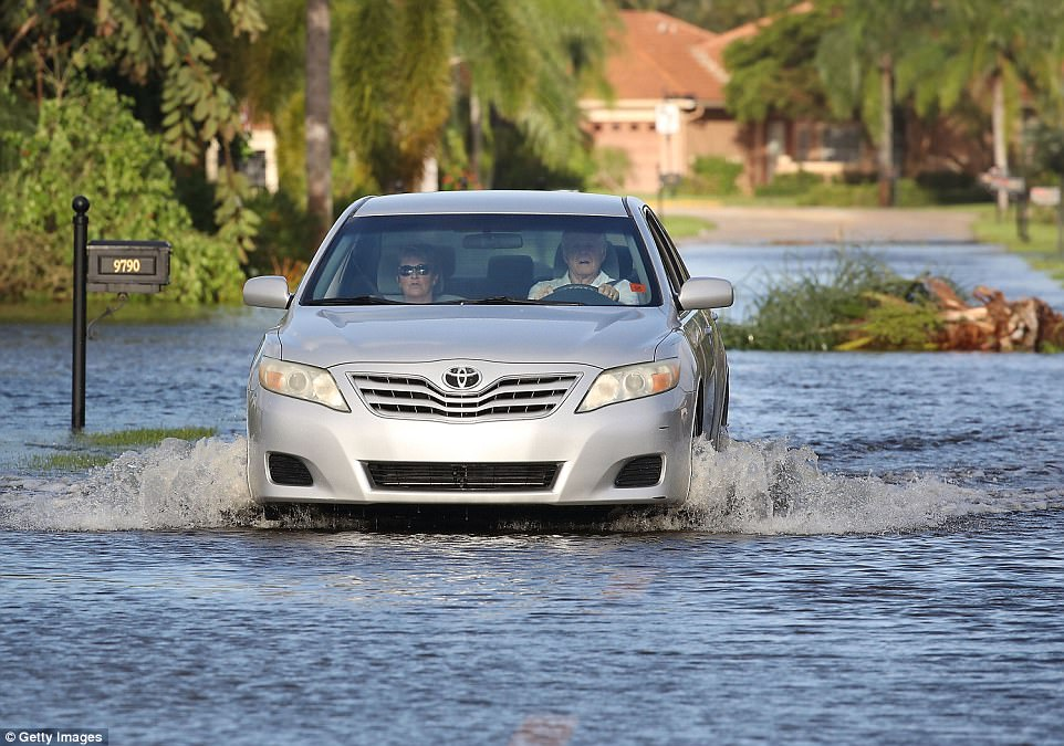 People drive through a neighborhood that was flooded by Hurricane Irma on September 11, 2017 in Bonita Springs, Florida