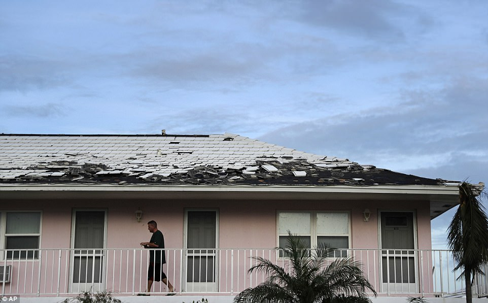 Tony Loduca walks back to his apartment past a roof whose tiles where torn off from Hurricane Irma in Marco Island, Florida on Monday