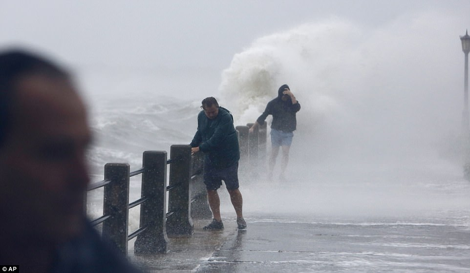 Pedestrians try to walk as waves crash at The Battery as Tropical Storm Irma hits Charleston, South Carolina on Monday