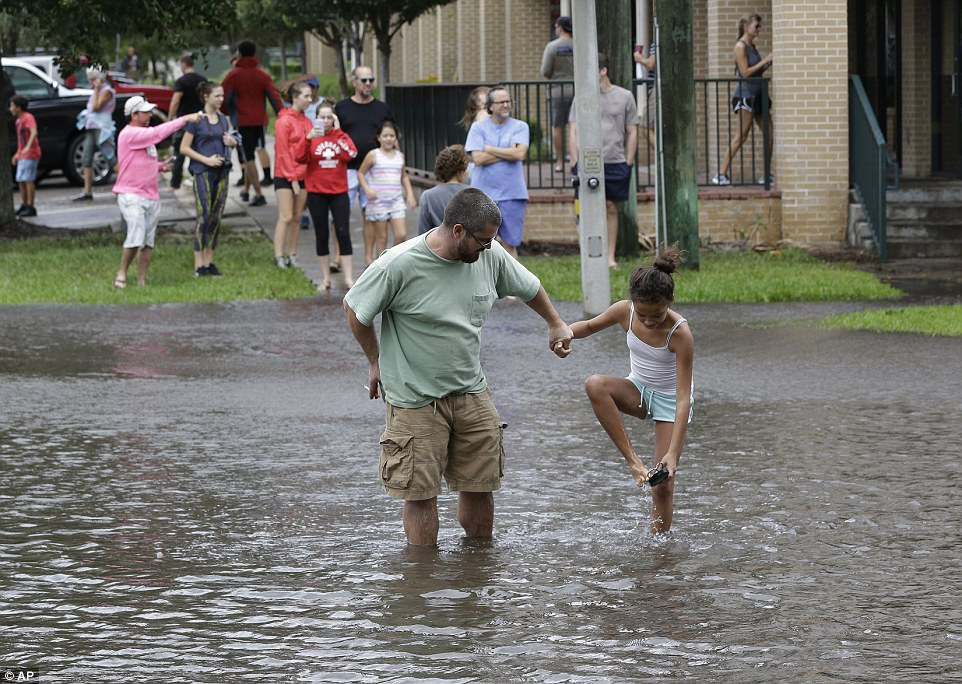 Residents make their way across a flooded street after Hurricane Irma brought floodwaters to Jacksonville, Florida Monday, Sept. 11, 2017