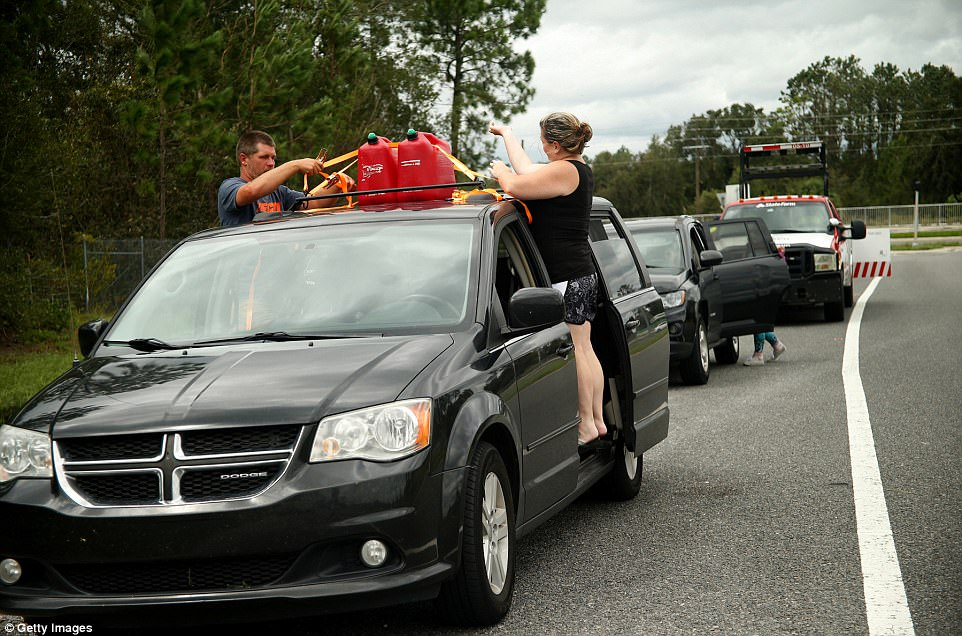 With no gas stations open anywhere in the area, motorists running low on fuel stop at an on ramp to westbound I-4 to refuel from tanks strapped to their vehicle's roof on September 11, 2017 in Lake Helen, Florida