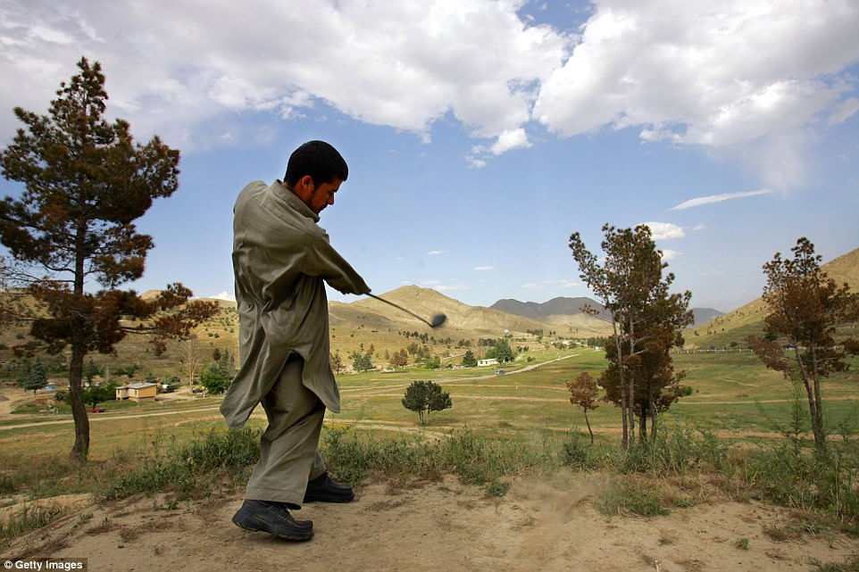 An Afghan golfer tees off on the 2nd hole at the Kabul Golf Club.It costs $  15 to play the entire course