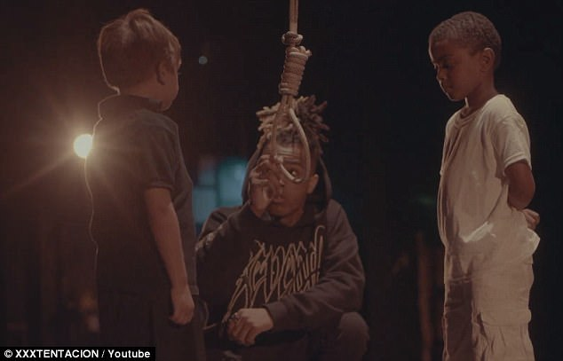 The rapper claims the video decries racial violence across the board and says the lynching scene is a part of that. The video then shows XXXTentacion showing a noose to the two children