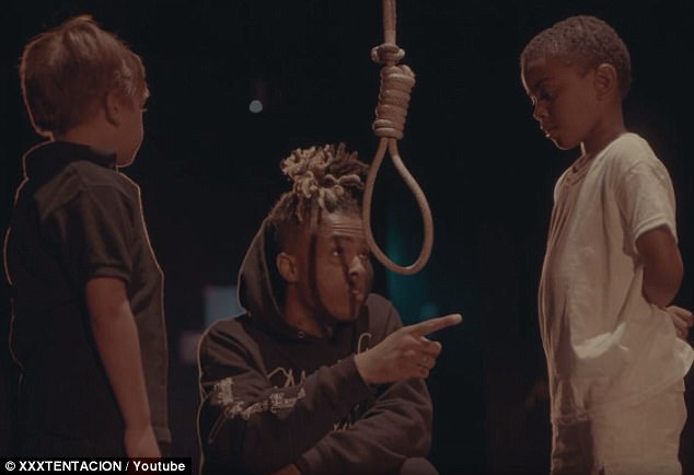 He insists he is trying to demonstrate what the lasting effects will be on the younger generation if the same violence continues. At one point, he points to the black child and tells him something before wrapping the noose around the white child's neck