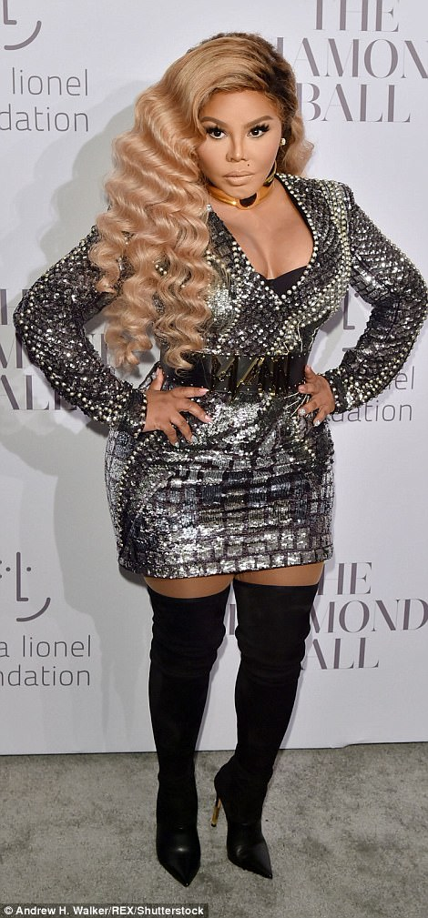 Blonde bombshell: Rapper Lil Kim squeezed herself into a metallic mini dress with thigh-high boots