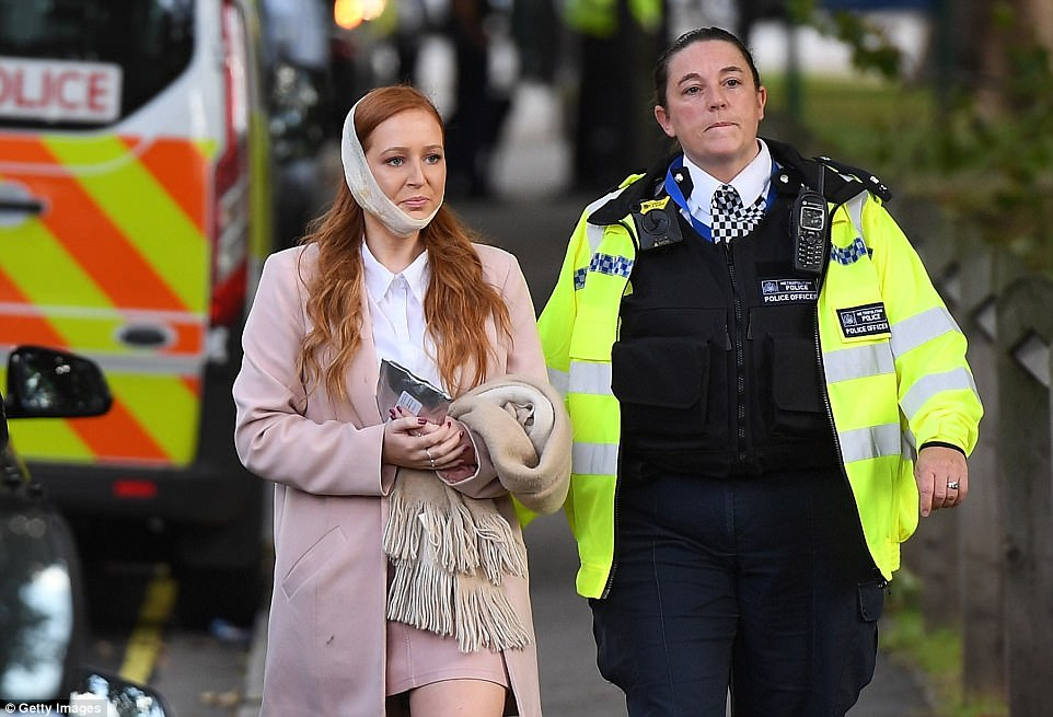 A well-dressed young woman was walked to safety by a Met officer after having her head bandaged after suffering a burn or wound to her cheek