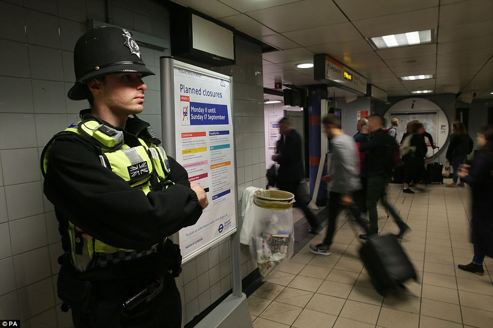 A police officer watches on as commuters file into the underground at Euston Station amid newly tightened security