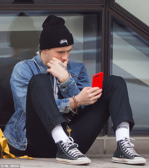 He's staying grounded: Brooklyn Beckham was spotted resting on the sidewalk outside Parsons School of Design as he waited to meet his mother Victoria in New York City on Friday