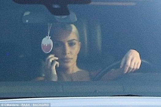 Is that legal? Kim Kardashian appears to be chatting on her photo when behind the wheel of her car in Los Angeles on Friday