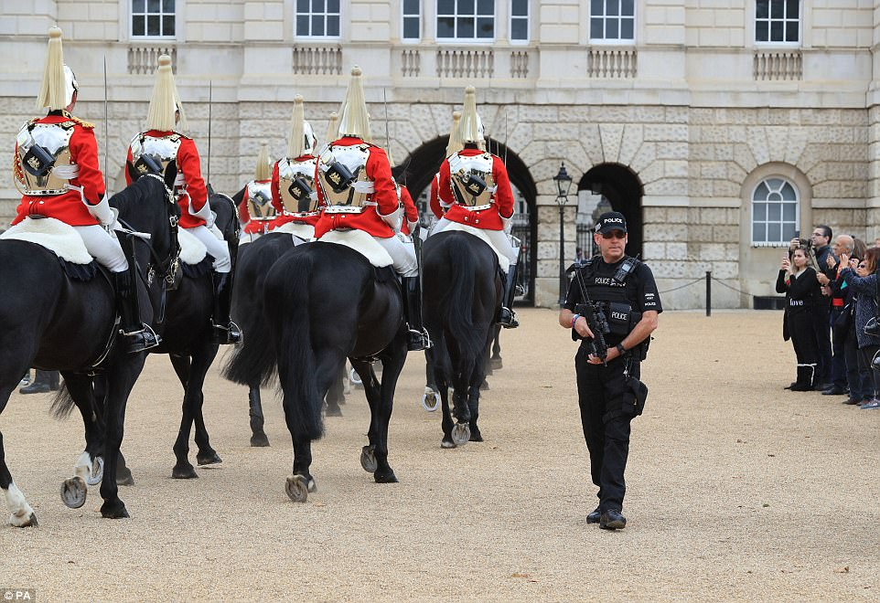 An armed police officer provides security as members of the Queen's Life Guard ride across Horse Guards Parade