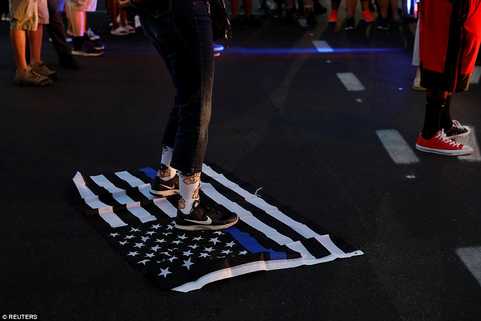 A protester stands on a 'blue lives matter' flag after the not guilty verdict in the murder trial