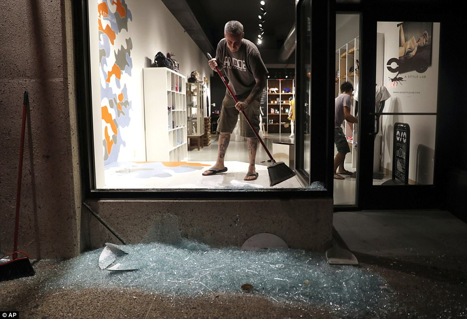 Local man Scott McRoberts helps clean up broken glass after a violent crowd broke windows on many businesses in University City