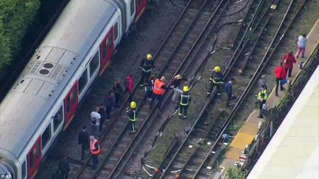 Passengers are ushered across the track by firefighters after getting trapped in the aftermath of the bombing on Friday morning