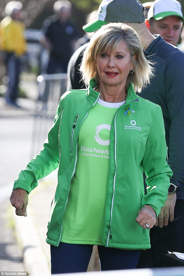 Bright: Dressed in a lime-coloured ONJ Cancer wellness and Research Centre track suit top over a matching T-shirt in a lighter shade of green, she seemed fit and happy