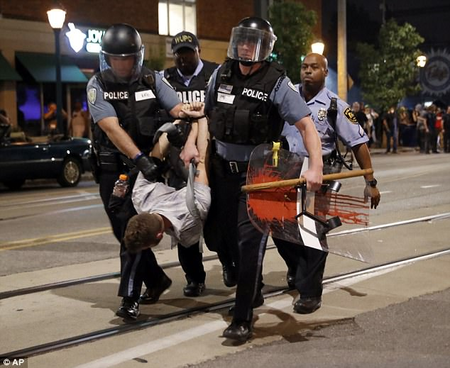 Police arrest a man as they try to clear a violent crowd on Saturday night in University City, Missouri