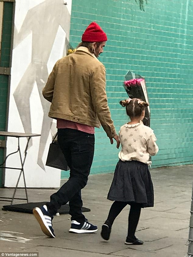 Bonding day: The handsome former football ace looked dressed casually in a tan sheepskin jacket and red T-shirt, and held Harper's hand as she skipped down the street
