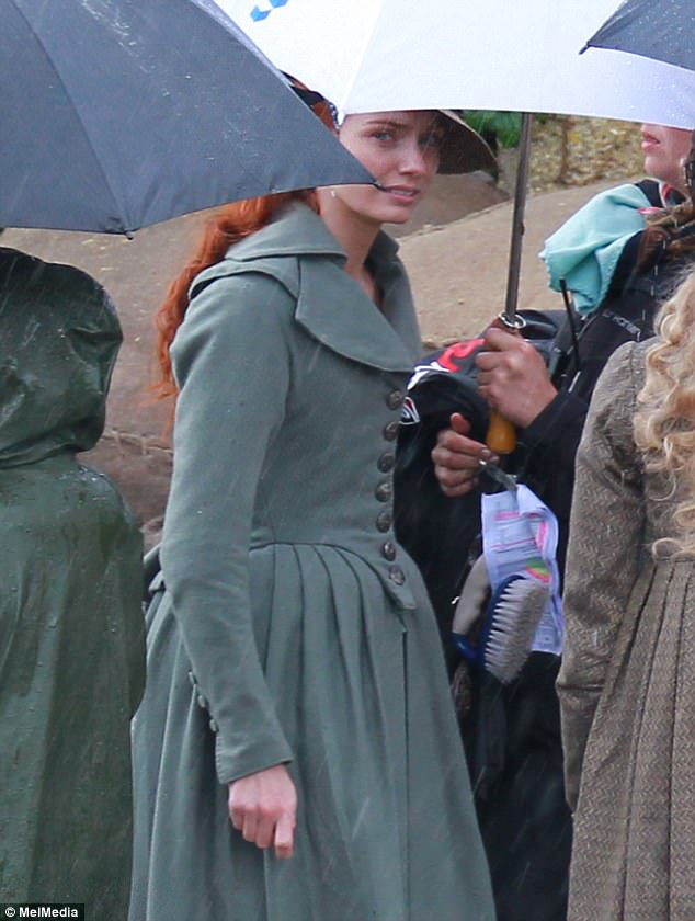 Taking cover:Aidan's on-screen wife Eleanor Tomlinson was also spotted on the rainy set, wearing her beautiful red hair in curls characteristic of Demelza Poldark