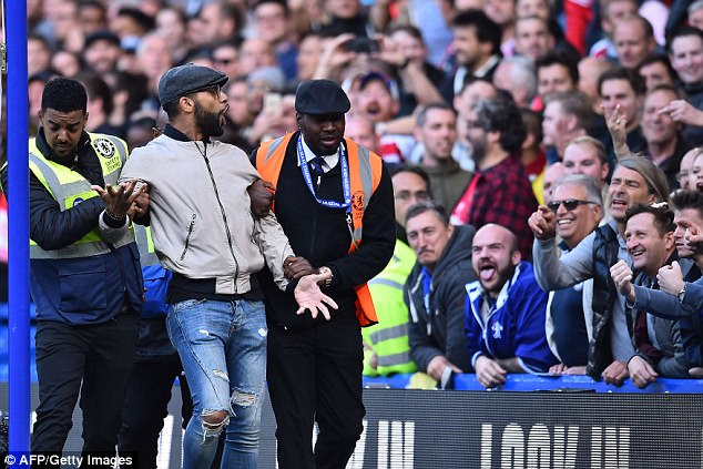 An Arsenal supporter is led away after running onto the pitch to celebrate a disallowed goal