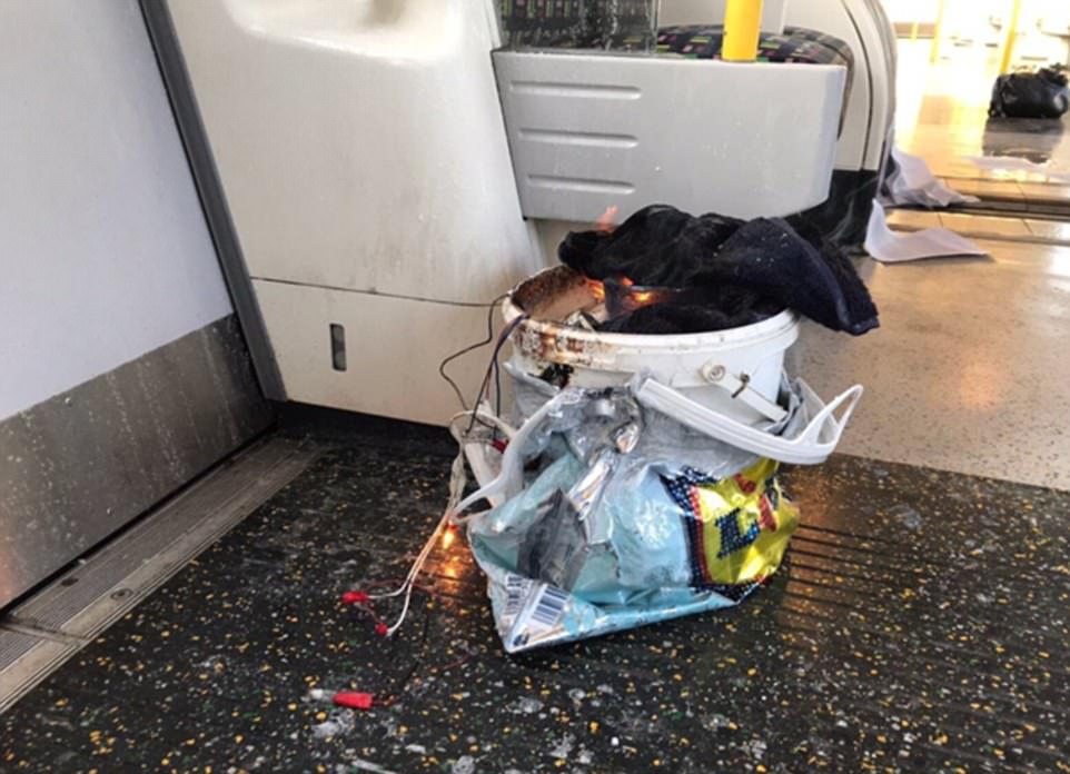 A photograph of the flaming white bucket taken just after it exploded around 8.20am on Friday shows a number of wires protruding out of the top and on to the train carriage floor